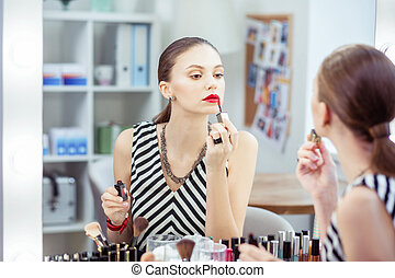 Beautiful nice young woman putting on her lipstick