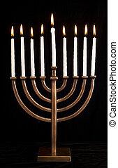 Beautiful lit hanukkah menorah on black velvet. Super black...