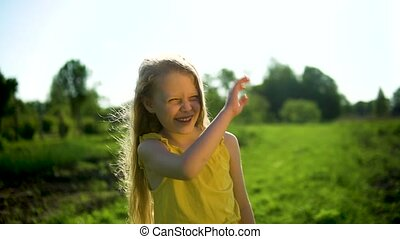 Beautiful little adult girl waving her hand with beautiful eyes concept well-being against the blue sky and green grass Hot Summer in nature