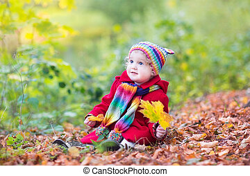 Beautiful little baby girl in a red jacket and knitted colorful