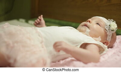 beautiful little baby girl lying on the bed