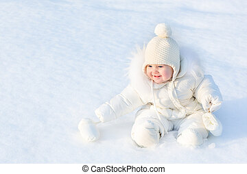 Beautiful little baby girl sitting in white snow wearing a warm