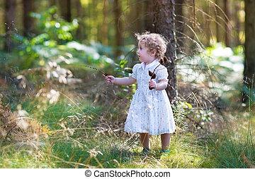 Beautiful little baby girl walking in a sunny autumn park wearin