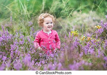 Beautiful little baby girl walking in purple autumn flowers in a