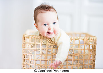 Beautiful little baby smiling out of a wicker basket