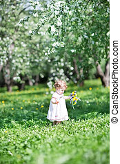 Beautiful little baby walking in a blooming garden