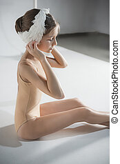 Beautiful little ballerina wearing a white swan bandage on her head
