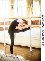little ballet dancer stretching in dance class