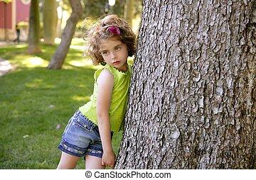 Beautiful little brunette girl beside a huge pine tree trunk