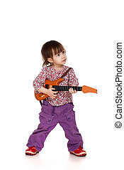 Beautiful little Caucasian girl plays with a guitar