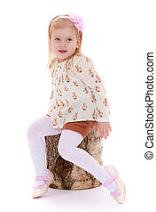 beautiful little Caucasian girl sitting in the woods on a birch