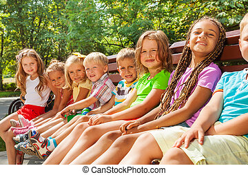 Beautiful little children sit on bench in park