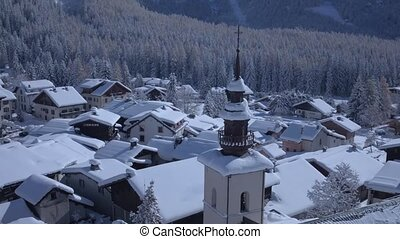 Beautiful little cozy house cottage villa in snow covered village in the Alps mountains aerial landscape on winter day