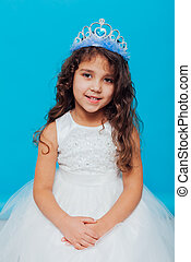 Beautiful little curly girl with crown tiara in white dress on a blue background background