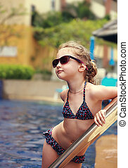 Beautiful little female model posing in sunglasses and swimsuit near swimming pool