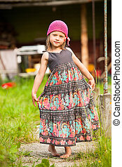 Beautiful little five-year girl posing for the camera in the yard of a village house.