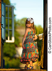 Beautiful little five-year girl posing for the camera on the porch of a village house at sunset