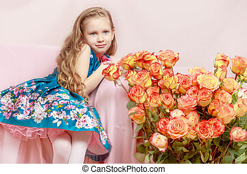 A beautiful little girl with long, light, curly hair, in a blue long skirt. She sits on a pink couch beside a large bouquet of tea roses.