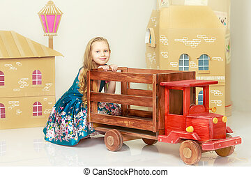 Beautiful little girl with long blond hair in a smart blue dress. Girl playing with a toy wooden car in a cardboard house.