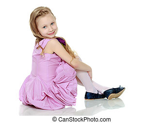 Happy little blond girl, with long curly hair, in a beautiful pink dress above the knees. She is sitting on the floor smiling at the camera.