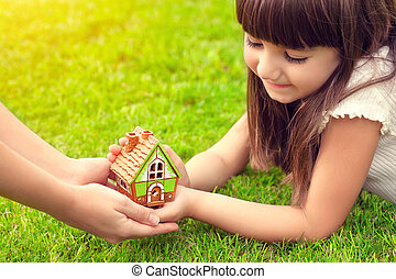 beautiful little girl and a woman hands holding small house on a background of green grass