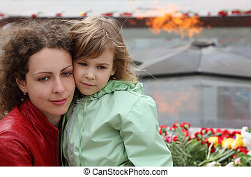 beautiful little girl and mother stands near memorial, eternal flame, focus on mother