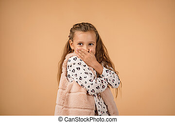 child closes her mouth with her hand
