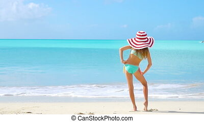 Cute little girl in hat at beach during caribbean vacation. Back view of adorable kid on the seashore. SLOW MOTION