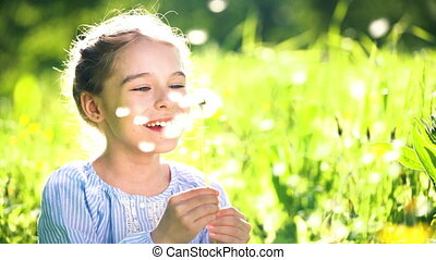 Beautiful little girl blowing dandelion at summer day. -...