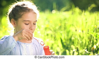 Beautiful little girl blowing soap bubbles at summer day. -...