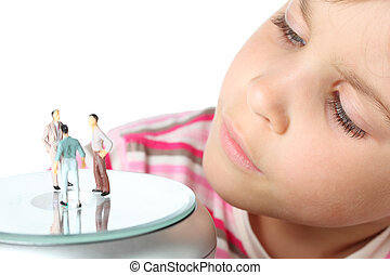 beautiful little girl carefully looks at small toy figures of man isolated on white