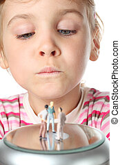 beautiful little girl carefully looks at small toy figures of people isolated on white