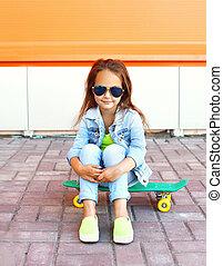 Beautiful little girl child sitting on skateboard in city