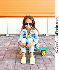 Beautiful little girl child sitting on skateboard in city