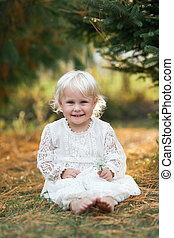 Beautiful Little Girl Child Smiling and Posing Outside under the Pine Trees
