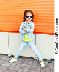 Beautiful little girl child wearing a sunglasses and jeans clothes in city