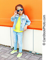 Beautiful little girl child wearing a sunglasses and jeans clothes over colorful background