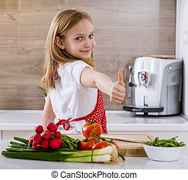 Beautiful little girl cooking in the kitchen and showing thumbs.