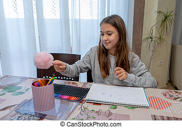 Beautiful little girl drawing funny at the table in her living room. Selective focus.