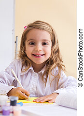 Beautiful little girl draws sitting at table