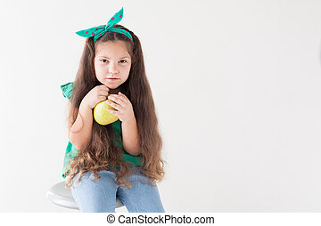 beautiful little girl eating a Green Apple fruit