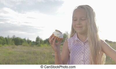 Beautiful, little girl eating brownie