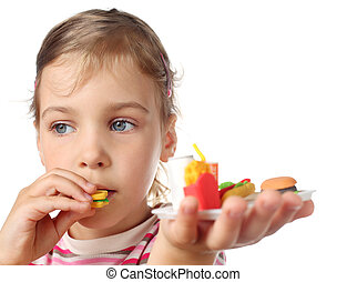 beautiful little girl eating toy miniature burger and keeps...