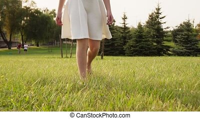 Beautiful little girl goes barefoot on grass in sunny summer...