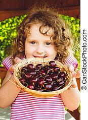 Beautiful little girl holding a basket of sweet cherries.
