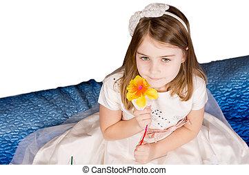 Beautiful little girl holding a flower