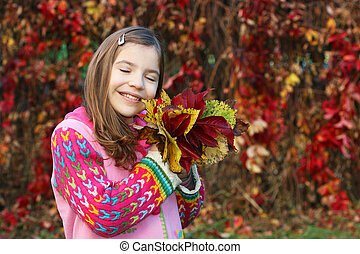 beautiful little girl holding colorful autumn leaves