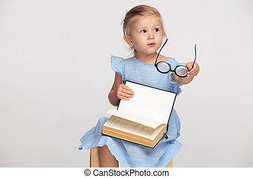 beautiful little girl holding her book and glasses while sitting