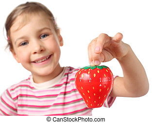 beautiful little girl holding red timer in shape of strawberries isolated on white, focus is on timer