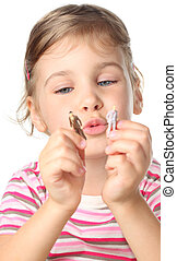 beautiful little girl holding small toy figures of people ...